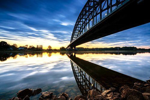 Spiegelde brug in de IJssel bij zonsopkomst