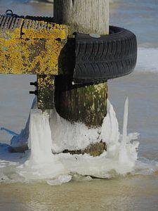 Aanlegpaal in het ijs bij het Lauwersmeer op een winterse dag