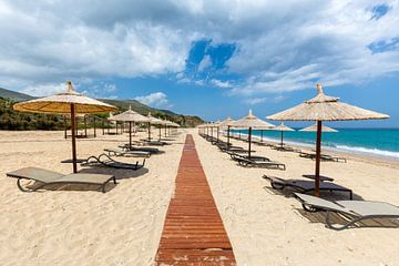 Sonnenschirme und Liegebetten oder Bahren am Strand auf der Insel Kefalonia in Griechenland von