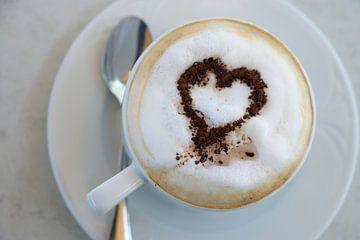 Tasse Cappuccino mit Kakaopulver in Herzform auf einem Tisch in einem Straßencafé, Hochwinkelansicht von Maren Winter
