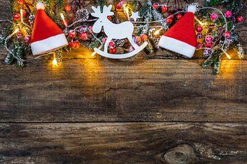 Traditionele kerstversiering met kerstmuts, rendier, dennentakken, rode bessen, dennenappels van Alex Winter