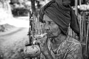 Alte faltige Frau raucht traditionelle Stumpen Zigarre vor ihrem Haus in Baghan in Myanmar