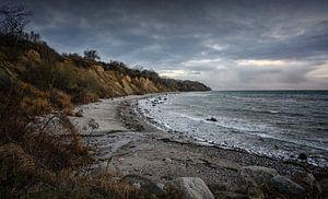 Steilküste mit Strand, Steinen und Wellen unter dunklem Wolkenhimmel an der Ostsee in Mecklenburg-Vo