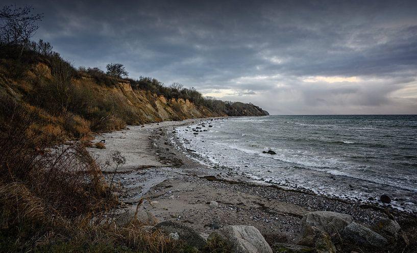 Steilküste mit Strand, Steinen und Wellen unter dunklem Wolkenhimmel an der Ostsee in Mecklenburg-Vo von Maren Winter