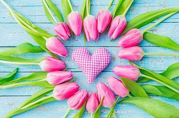Roze hart en tulpenbloemen op blauwe houten achtergrond voor Moederdag van Alex Winter