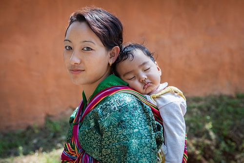 Jonge bhutanese vrouw mat baby op rug in Wangdi Bhutan. Wout Kok One2expose van