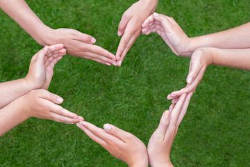 Veel handen van kinderen vormen hart boven gras van