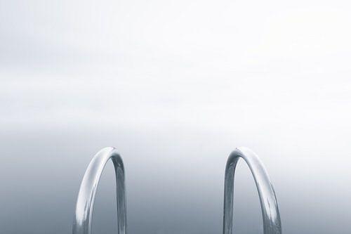 Abstracte zwart-wit foto van een metalen trap bij een meer in de mist