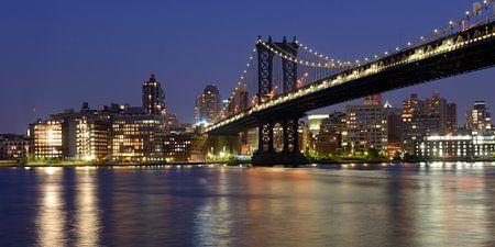 Manhattan Bridge over East River in New York in de avond, panorama