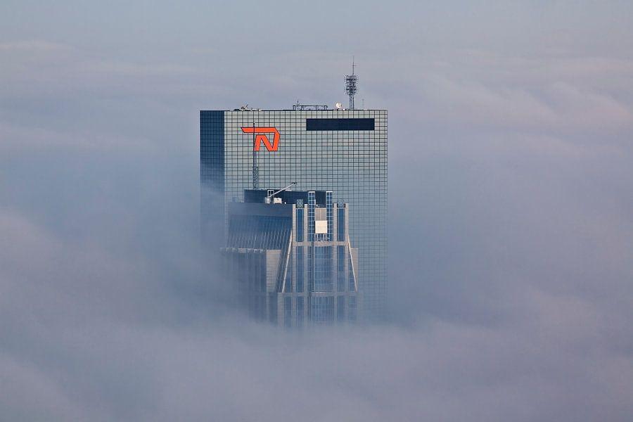 Gebouwen prikken door de mist te Rotterdam van Anton de Zeeuw