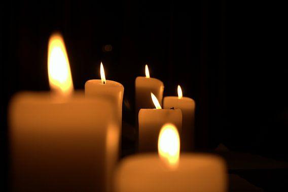 sechs brennende Kerzen in der Dunkelheit