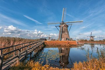 Des moulins à vent dans un paysage orange et bleu sur Leon Brouwer