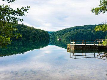 Nationalpark Kroatien. Spiegelung im Wasser mit Boot und Bergen im Hintergrund von Déwy de Wit
