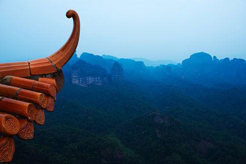Dak van Chinese tempel met op de achtergrond blauwe bergen