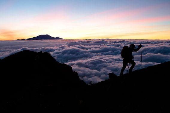 Een bergbeklimmer op de Mount Meru, met de Kilimanjaro op de achtergrond. De opkomende zon zet het landschap in een magisch paars roze licht.