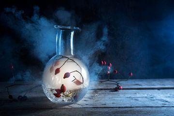fles met gloeiende rook en rozenbottels binnenin op een rustieke houten tafel tegen een donkerblauwe van Maren Winter