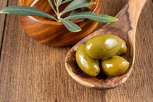 Groene olijven op een houten lepel