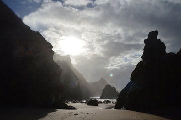 Eerste zonnestralen door de bergen op het strand. van Eline Slijkhuis