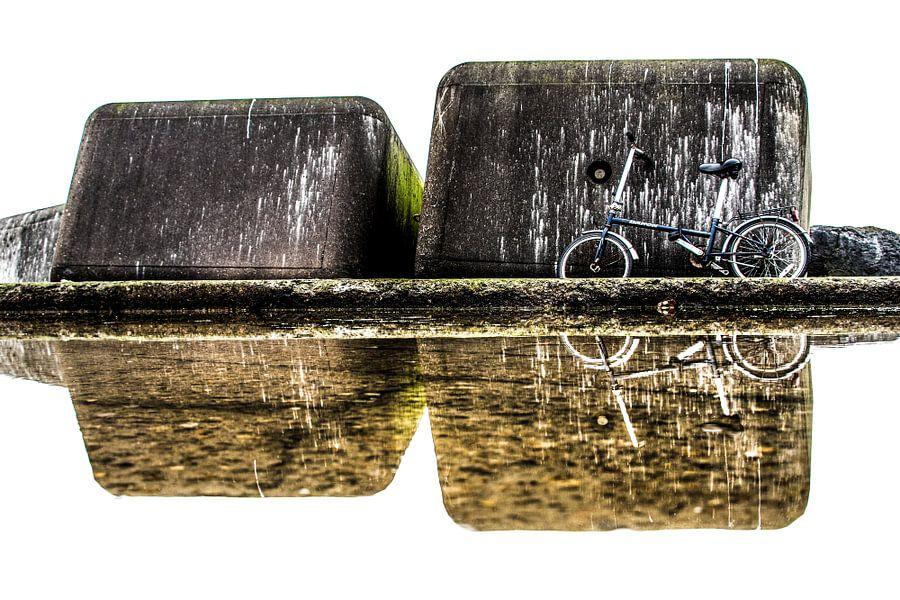 Betonblokken en fiets weerspiegeld in een plas op de Zuidpier