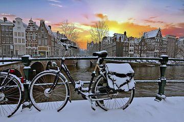 Paysage de la ville enneigée d'Amsterdam au coucher du soleil sur Nisangha Masselink