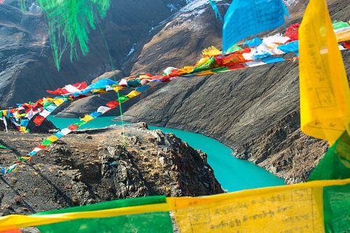 Kijk door de gebedsvlaggetjes naar de rivier, Himalaya