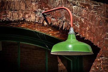 Groene metalen lamp op een stenen muur. van Jan van Dasler