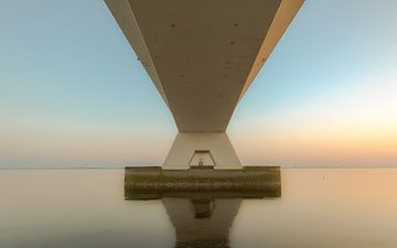 Zeeland bridge during serene sunset sur Sander Hupkes