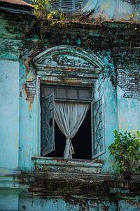 Een prachtig raam van een vervallen kolonistisch gebouw in Myanmar