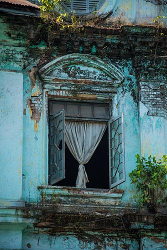 Een prachtig raam van een vervallen kolonistisch gebouw in Myanmar van