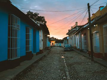 Orangefarbener Sonnenaufgang in einer Straße in Trinidad de Cuba mit einem Oldtimer