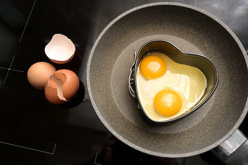 Twee gebakken eieren in hartvorm op een koekenpan en lege schalen op het zwarte fornuis, koken met l van Maren Winter