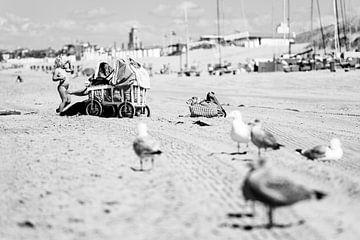 Eine Mutter am Strand von Katwijk aan Zee reibt ihr Kind mit Sonnenschutzmitteln; im Vordergrund lau von Evert Jan Luchies