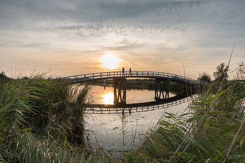 Stel loopt over de zijdebrug bij zonsondergang