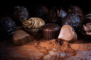 Chocoladepralines en cacaopoeder op rustiek hout als liefdesgeschenk, close up tegen een donkere ach van Maren Winter