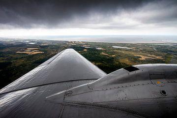 klassiek DC-3 vliegtuig vliegend langs de Nederlandse kustlijn van Jeffrey Schaefer