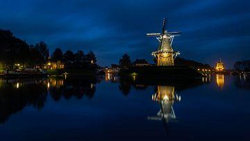 Verlichte molens van Dokkum bij avond weerspiegeld van