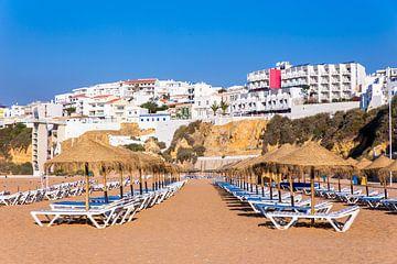 Reihen der Strandschirme mit Wohnungen auf Küste bei Albufeira in Portugal von