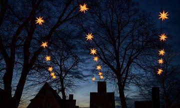 Verlichte Herrnhuter Moravische Kerststerren die boven de donkere silhouetten van oude huisgevels en van Maren Winter