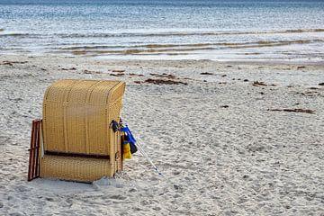 strandstoel met krukken die ertegen leunt in het zand bij de zee, zomervakantie van mensen met speci