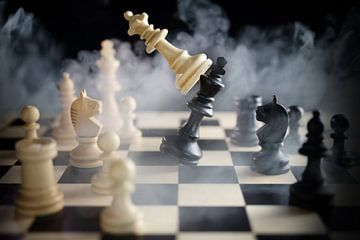 schaakkoningin verslaat koning tussen andere stukken op het schaakbord, veel rook over de strijd, te van Maren Winter