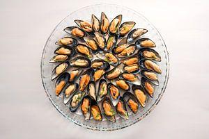Mosselen gekookt met ui en kruiden geserveerd op een rond glazen bord, grijze achtergrond met kopiee