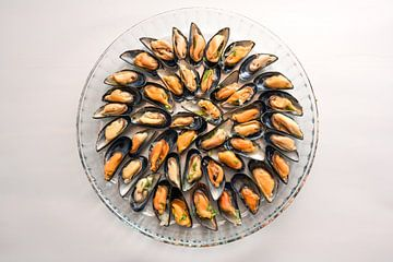 Mosselen gekookt met ui en kruiden geserveerd op een rond glazen bord, grijze achtergrond met kopiee van Maren Winter