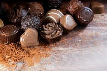 Fijne chocoladepralines op cacaopoeder als liefdesgeschenk, hoekachtergrond met kopieerruimte op rus van Maren Winter