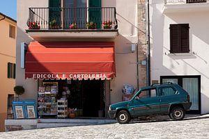 Fiat Panda geparkeerd bij boekwinkel in Italië