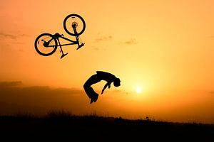 Stunt fietser bij zonsondergang van