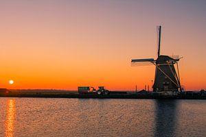 Hollands plaatje met molen, een tractor en zonsondergang van