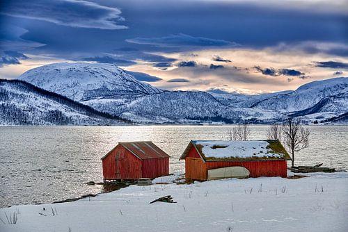 Winterlandschaft mit typischen rotem Hause an der schneebedeckten Kueste