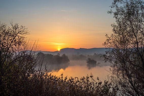 Zonsopkomst boven heuvels bij een rivier