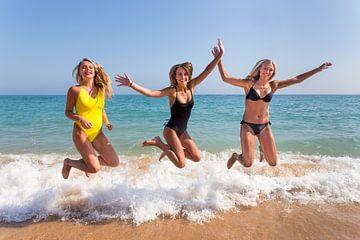 Drie meisjes springen op strand bij zee van Ben Schonewille