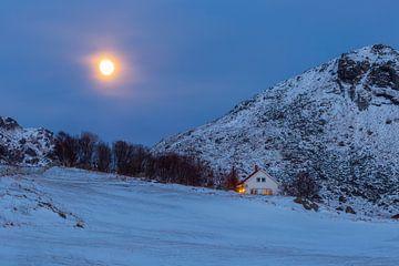 Une maison à la lumière agréable sur une pente de montagne enneigée sous la pleine lune sur Sander Groffen